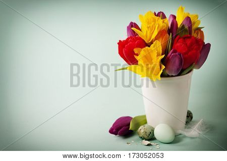 Spring flowers and easter eggs over blue