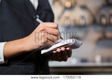Mid section of bartender writing down an order in bar