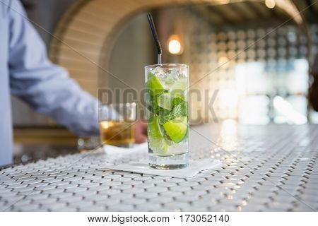 Glass of gin on bar counter and man standing in background