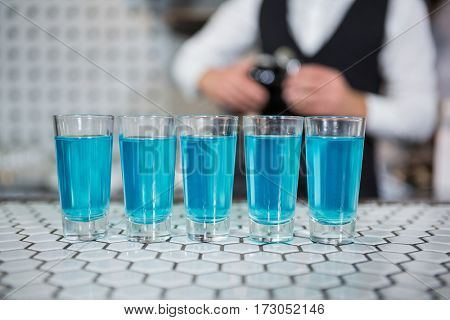 Glass of blue lagoon drinks on bar counter and bartender standing in background