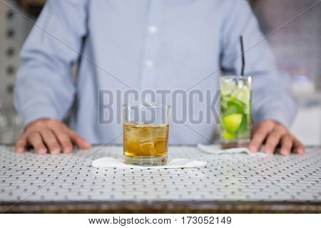 Glass of whisky on bar counter and man standing in background