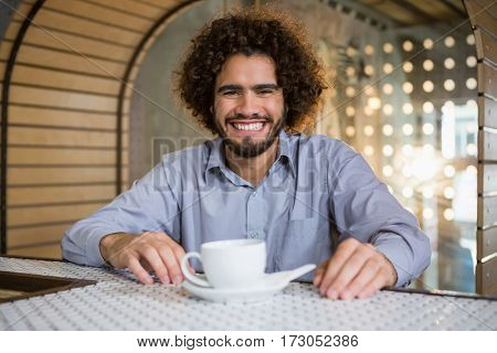 Portrait of man sitting on bar counter with cup of tea in bar