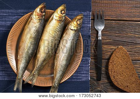 Smoked fish in plate with fork and bread on rustic table top view
