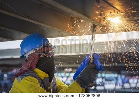 Worker cut the steel base for repair container Worker cutting metal with acetylene torch close-up on low ligth