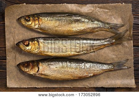 Smoked herring in paper on dark wooden table close up top view