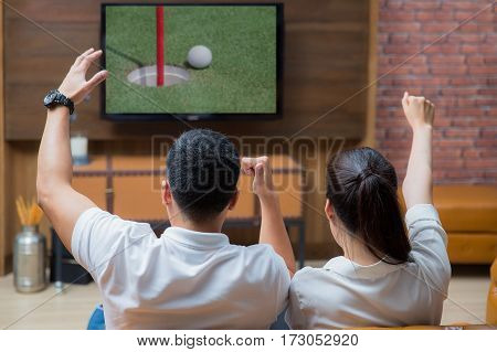 Asian Couple having fun watching golf game in living room