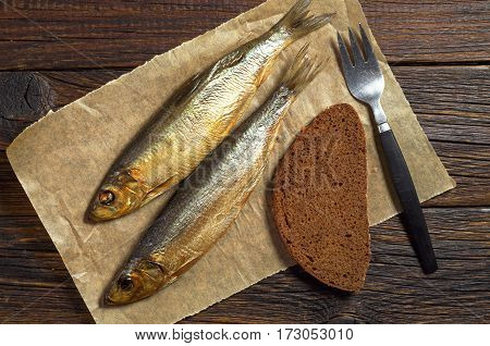 Smoked fish with fork and bread on dark wooden table top view