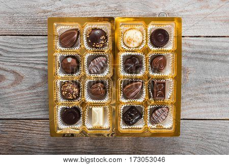 Assorted chocolates on a wooden background. Best sweets