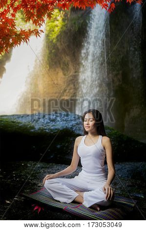 Young woman in yoga pose sitting near waterfall Rear view Yoga is a physical mental and spiritual practice or discipline which originated in India Yoga exercise and meditation with nature concept spa