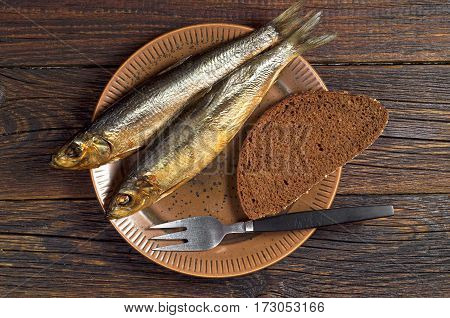 Smoked herring in plate with fork and bread on dark wooden table top view