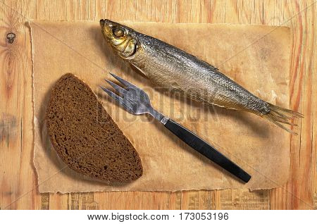 Smoked fish with fork and bread on old wooden table top view