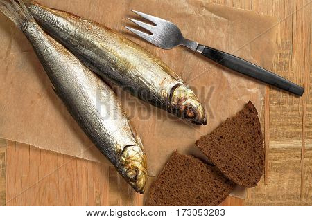 Smoked fish with fork and slice bread on old wooden table top