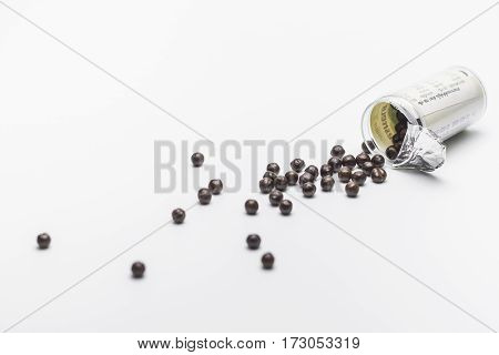 Black pills of traditional medicine Pills herb and plastic bottle on white background Copy space.