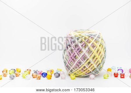 Colorful threads ball for knitting and beads on a white background Copy space.