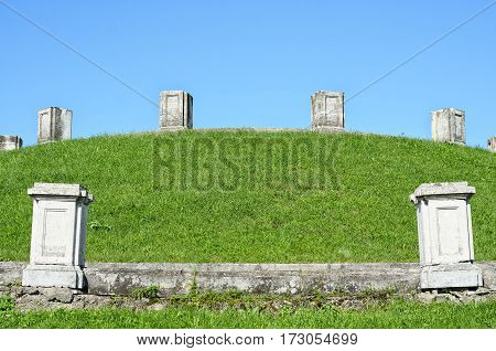 Ancient ruins colums. Blue sky and green grass.