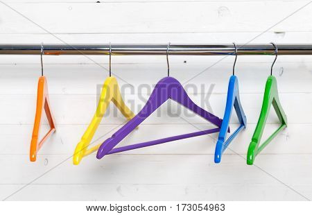 Group of multicolored hangers for garments on the black rack next to the white wall