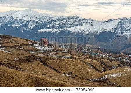 Constructions of the massive house in georgian mountain region, huge snow-covered mountains on the background