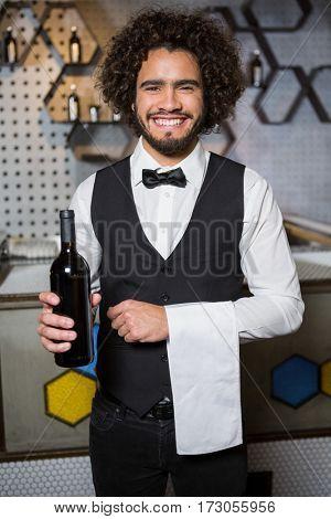 Portrait of smiling bartender serving bottle of wine in bar counter at bar