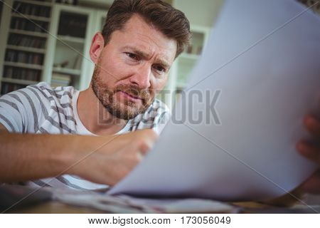 Worried man looking at his bills at home