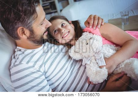 Father and daughter embracing on sofa at home