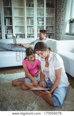 Mother and daughter sitting on floor and using digital tablet while father using laptop in background