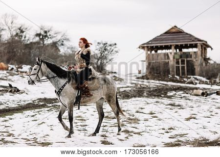 Viking girl on horseback mountain snow in the background