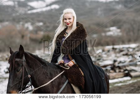 Beautiful blonde Viking in a black cape on horseback mountain snow in the background