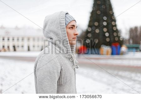 Handsome Man In A Stylish Knitted Clothes On A Background Of The Christmas Tree