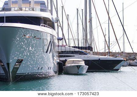 huge sailboat and small motor boat at the pier of the port of Rhodes