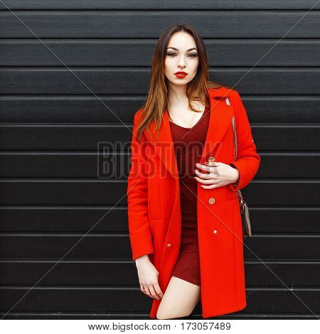 Beautiful Woman In Stylish Red Coat Next To A Black Wooden Wall