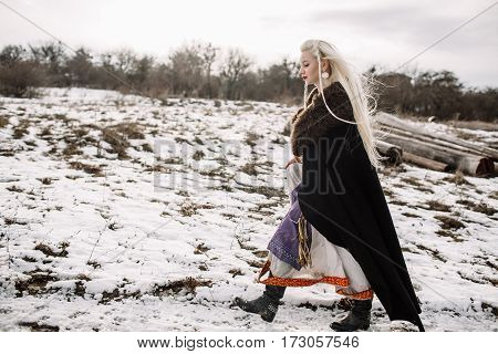 Portrait of a beautiful blonde in a black cape viking snow mountain in the background