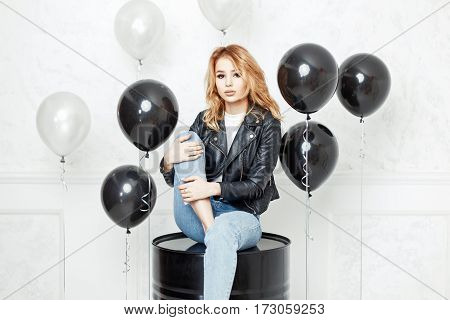 Pretty Woman In Stylish Black Leather Jacket And Blue Jeans Sitting On The Black Barrel. Black Ballo