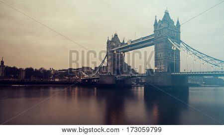 Tower Bridge with reflections in the thames river at sunset in London, United Kingdom, England