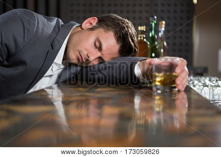 Drunk man lying on a counter with glass of whisky at bar