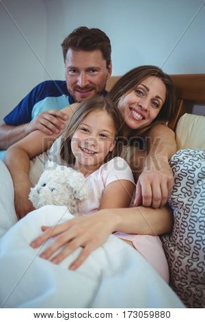 Parents lying on bed with daughter at home