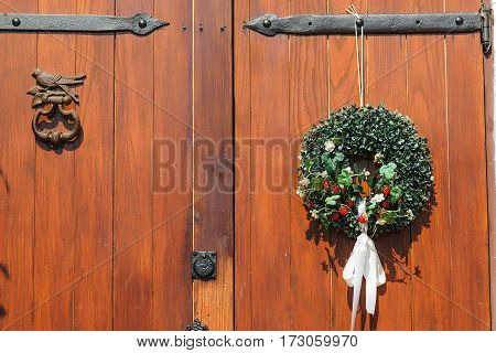Beautiful decorative wreath hanging on the wooden door.