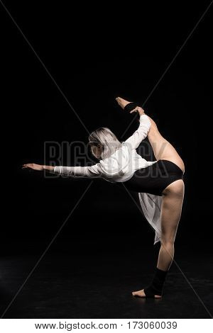 back view of woman in bodysuit dancing on black