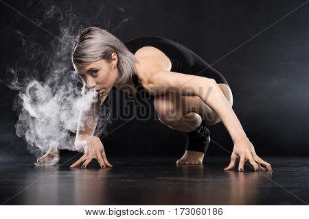 woman in bodysuit exhaling smoke on black