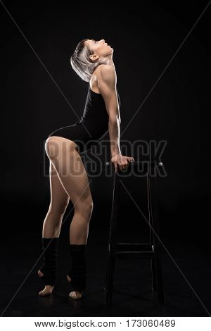 Side view of attractive sporty woman dancer posing with stool on black