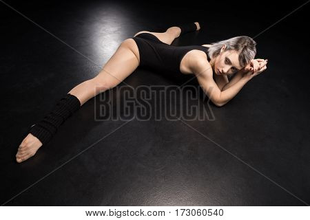 Attractive young woman contemporary dancer stretching on black