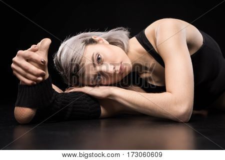 Attractive sporty young woman dancer stretching and looking at camera