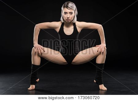 Sporty young woman contemporary dancer posing and looking at camera