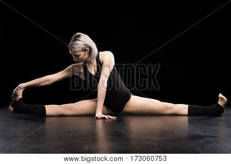Attractive young athletic woman dancer stretching on black