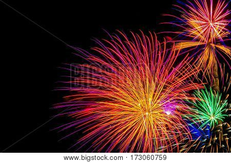 Colorful fireworks shot off in the night sky on the right side of the picture