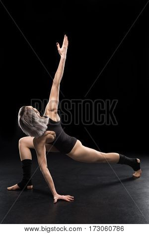 Young athletic woman contemporary dancer posing on black