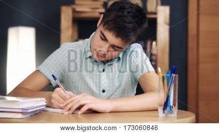 Teenager makes lessons and writes at home on dark background