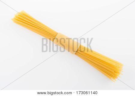 top view of raw vermicelli italian pasta on white