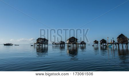 Silhouette and reflection scenery of sea gypsies or bajau laut house at Tebah Batang Village, Lahad Datu,Sabah,Borneo.Bajau laut native lives nomadic on the ocean horizon.