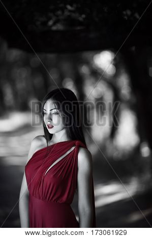 Wonderful sexy fashion model walking in a fantastical forest by footpath.Mystical portrait of sensual seductive woman in luxury long red dress posing against bokeh trees background. Multi-racial Asian Caucasian girl. Fashionable toning. Creative computer