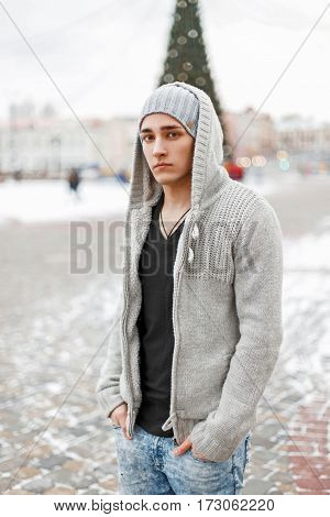 Stylish Young Man In A Hood And Knitted Sweater Posing In The City.